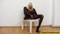 Horny blonde in black nylon toys herself with a big dildo