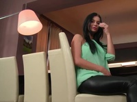 Young brunette is sexy leather pants fingers her pink slit