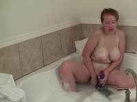 Chubby redhead is using an extra long dildo in the bathtub
