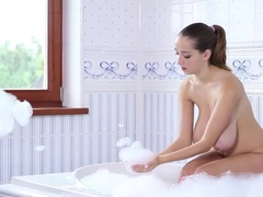 Coy girl with melons plays with herself and some bubbles